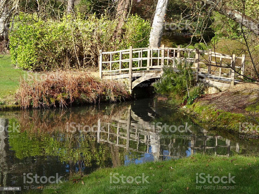 Image of arching timber bridge across shallow river, tree reflections stock photo