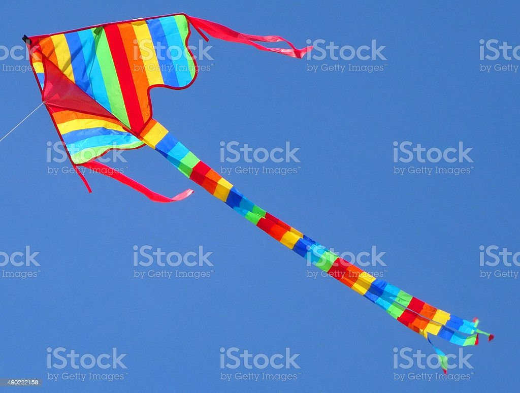 Image of arrowhead kite flying in sky with rainbow stripes stock photo
