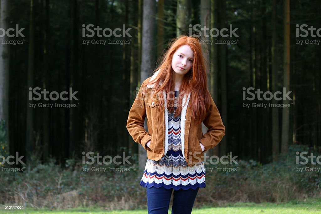 Image of attractive girl, long red hair, hands in pockets stock photo