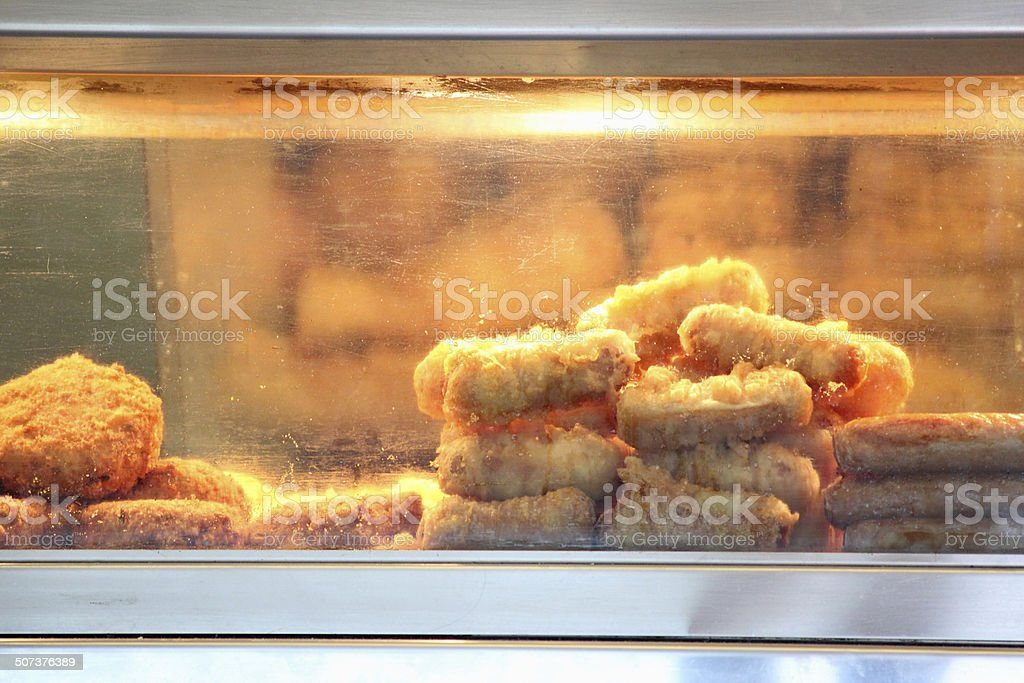 Image of battered sausages, fishcakes, fish and chip shop display stock photo