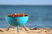 Image of beach barbecue, seaside BBQ, sausages, burgers, kebabs