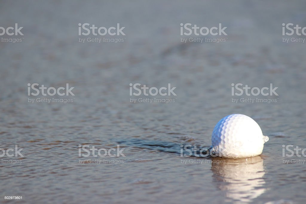 Image of beach golf / wet golf ball in water / sea stock photo