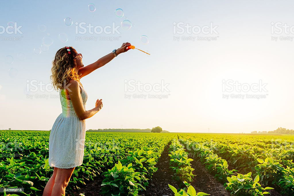 Image of beautiful attractive woman in organic farm blowing bubbles stock photo