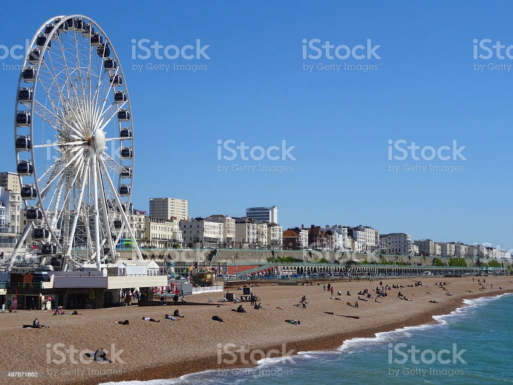 Image of big wheel attraction, beach and tourists in Brighton stock photo