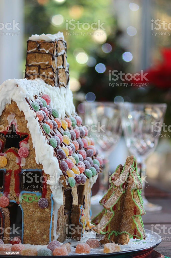 Image of biscuit gingerbread house with sweets as roof-tile decorations stock photo