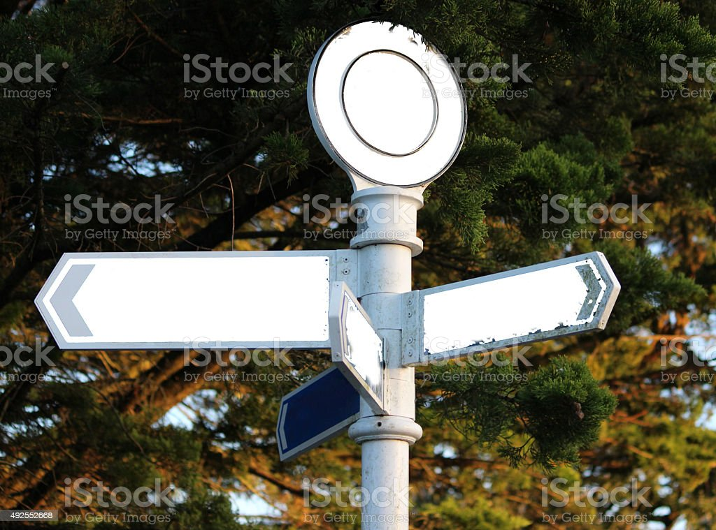 Image of blank white signpost with arrows pointing in-all directions stock photo