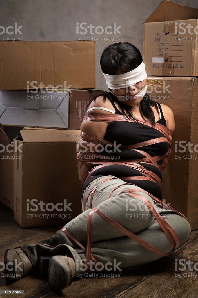 Image of blindfolded, tied up woman being kidnapped stock photo
