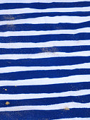 Image of blue and white striped beach mat at seaside