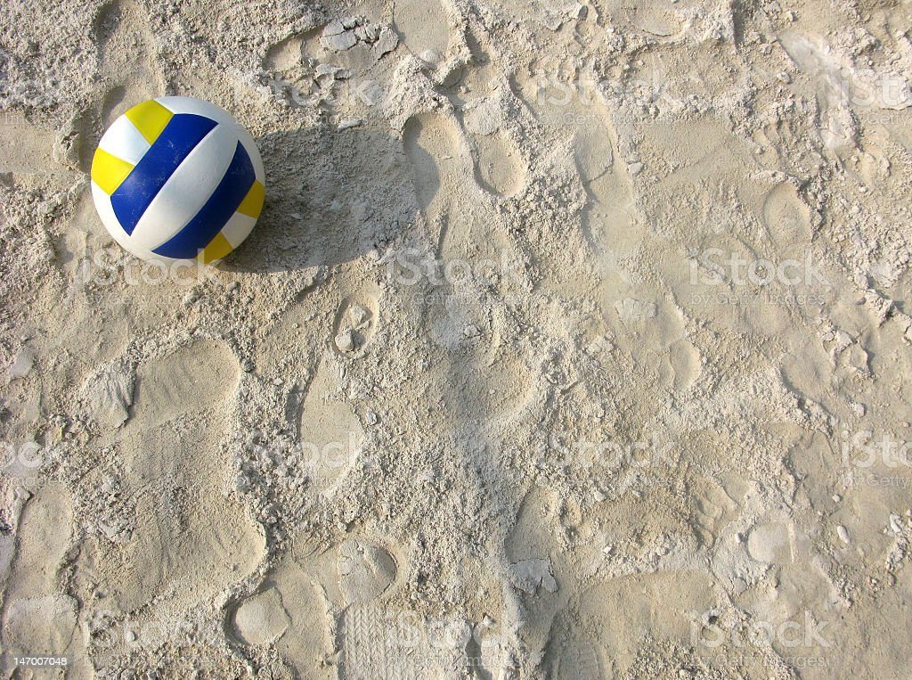 Image of blue and yellow volleyball in the sand stock photo