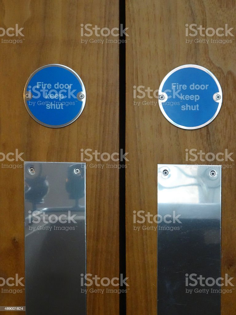 Image of blue circular safety 'Fire door keep shut signs' stock photo