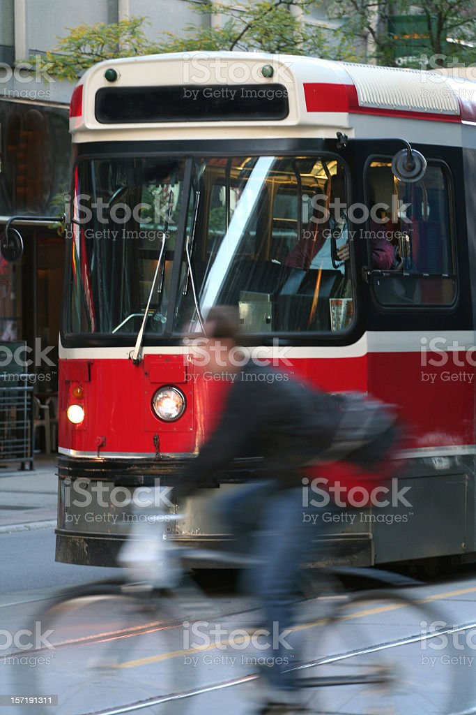Image of blurred man cycling past red tram royalty-free stock photo