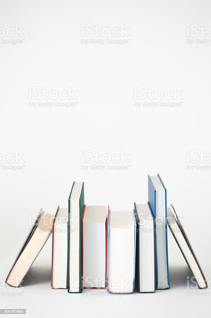Image of books placed in a row on white background stock photo