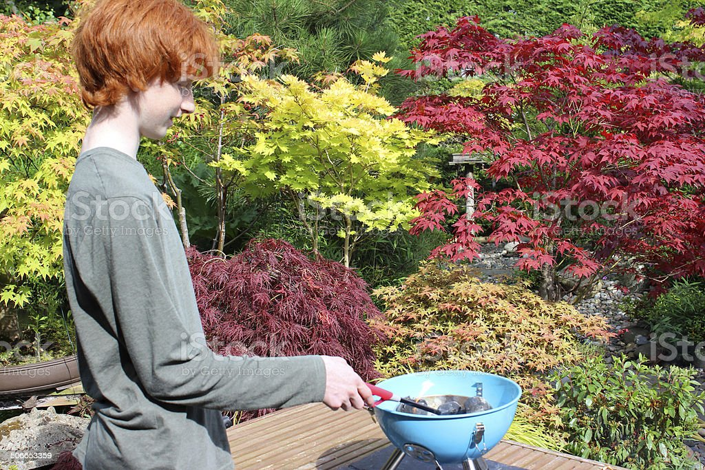Image of boy lighting portable charcoal barbecue / BBQ in garden stock photo