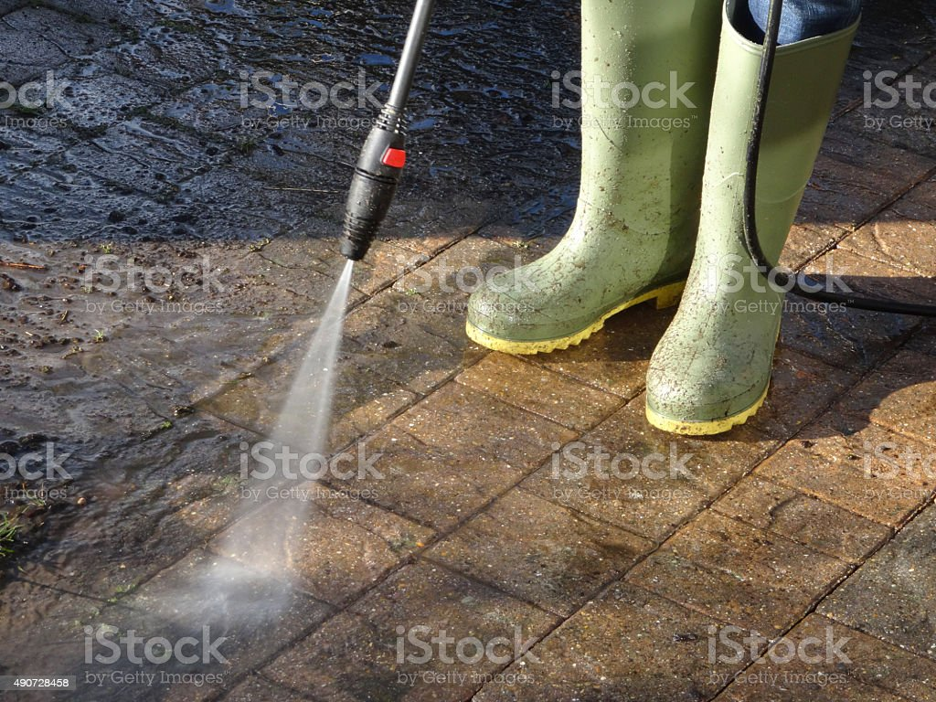 Image of boy washing driveway with pressurised powerwasher / pressure-washer nozzle stock photo