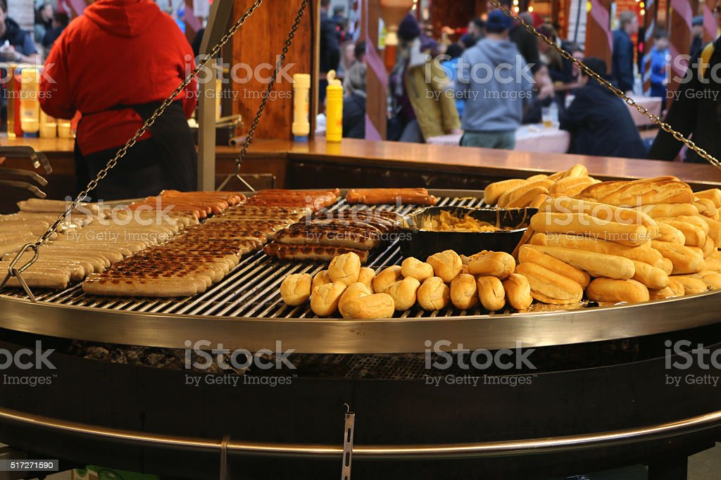 Image of bratwurst sausages and bread rolls warming on schwenkgrill stock photo