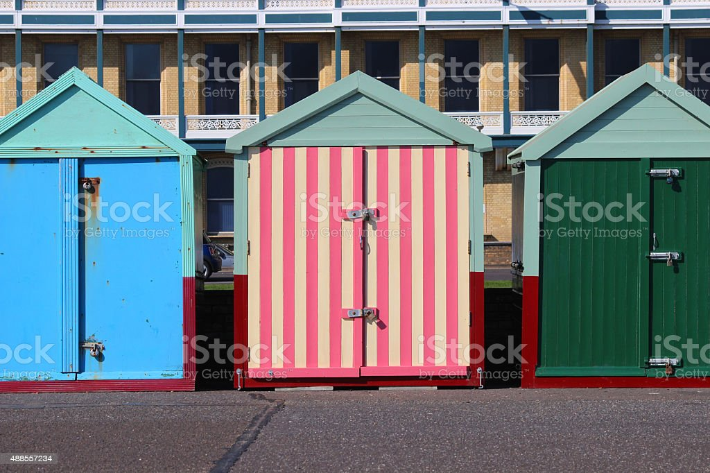 Image of Brighton beach huts with retro pink stripes front-door stock photo