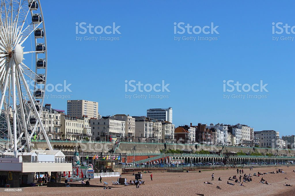 Image of Brighton beach, summer holiday-makers, tourists and sunbathers, big-wheel stock photo