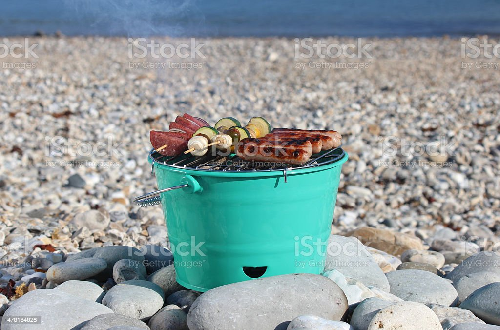 Image of bucket-shaped charcoal barbecue / BBQ on pebble beach, cooking-food stock photo