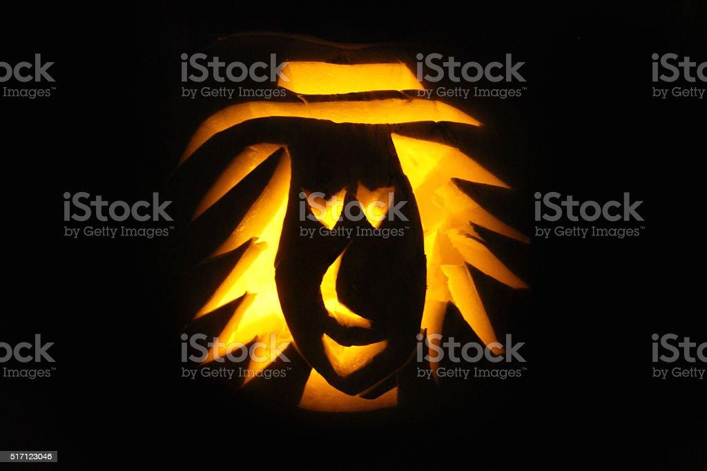 Image of carved pumpkin head, illuminated cartoon witch face, orange-glow stock photo