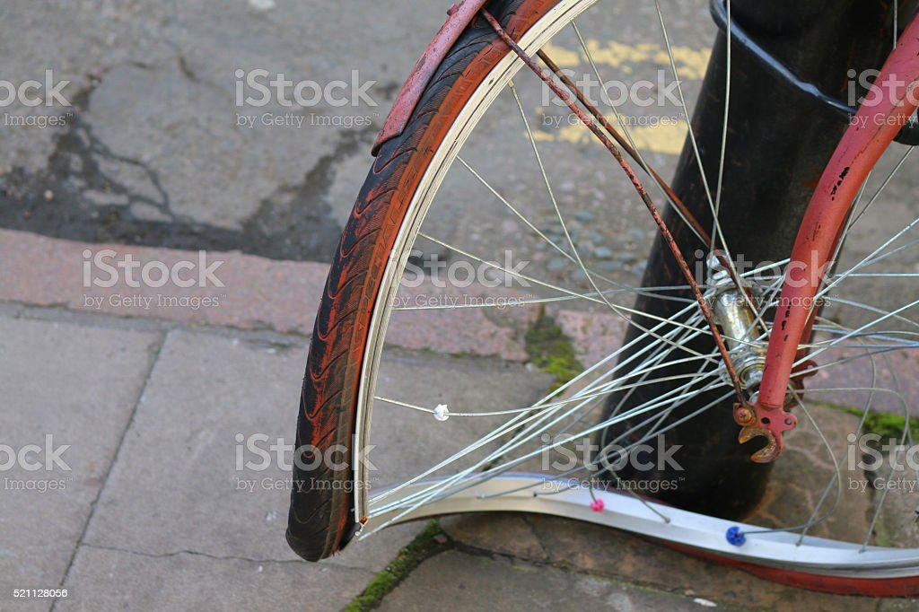 Image of chained bicycle with close-up of buckled front wheel stock photo