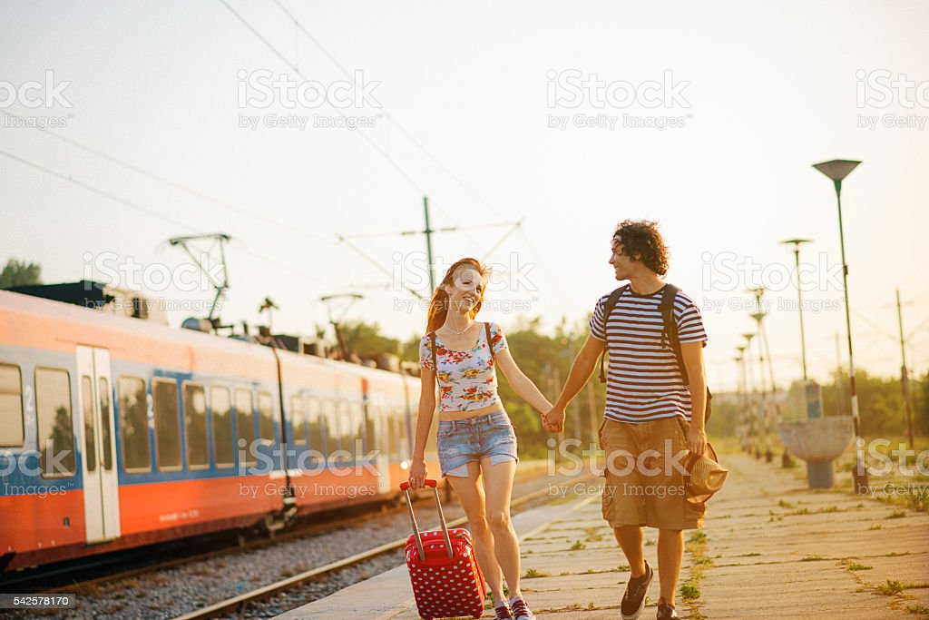 Image of cheerful couple traveling by train on summer adventure stock photo