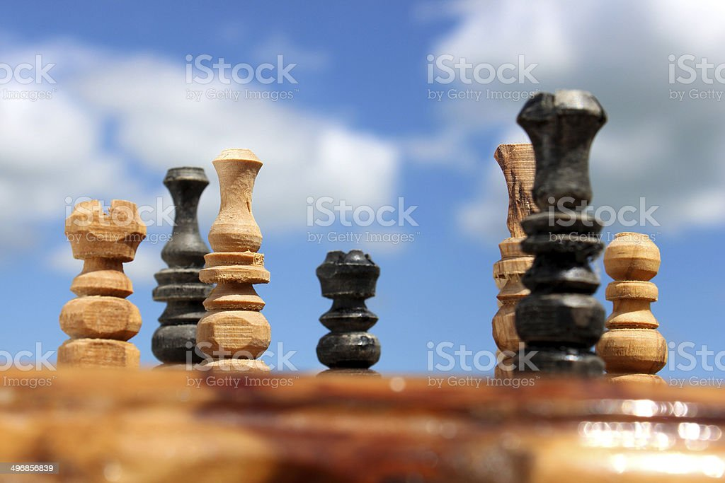 Image of chessboard game / wooden chess set against sky, boardgame stock photo