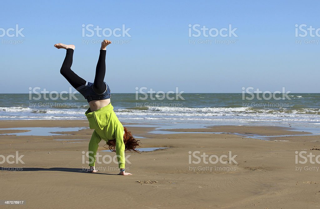 Image of child doing cartwheels on beach during seaside holiday stock photo