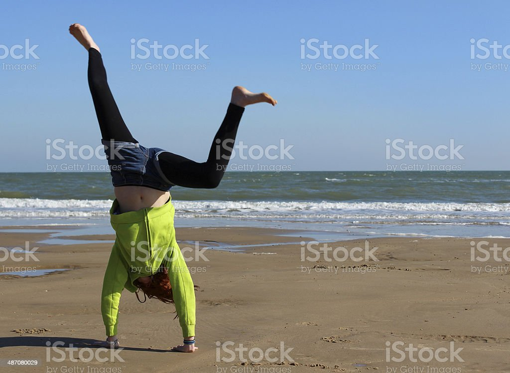 Image of child standing on hands doing cartwheel on beach stock photo