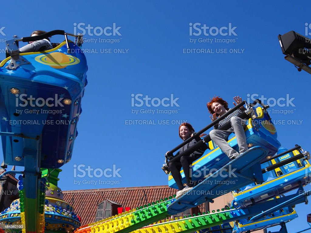 Image of children enjoying roundabout funfair ride on Brighton Pier stock photo