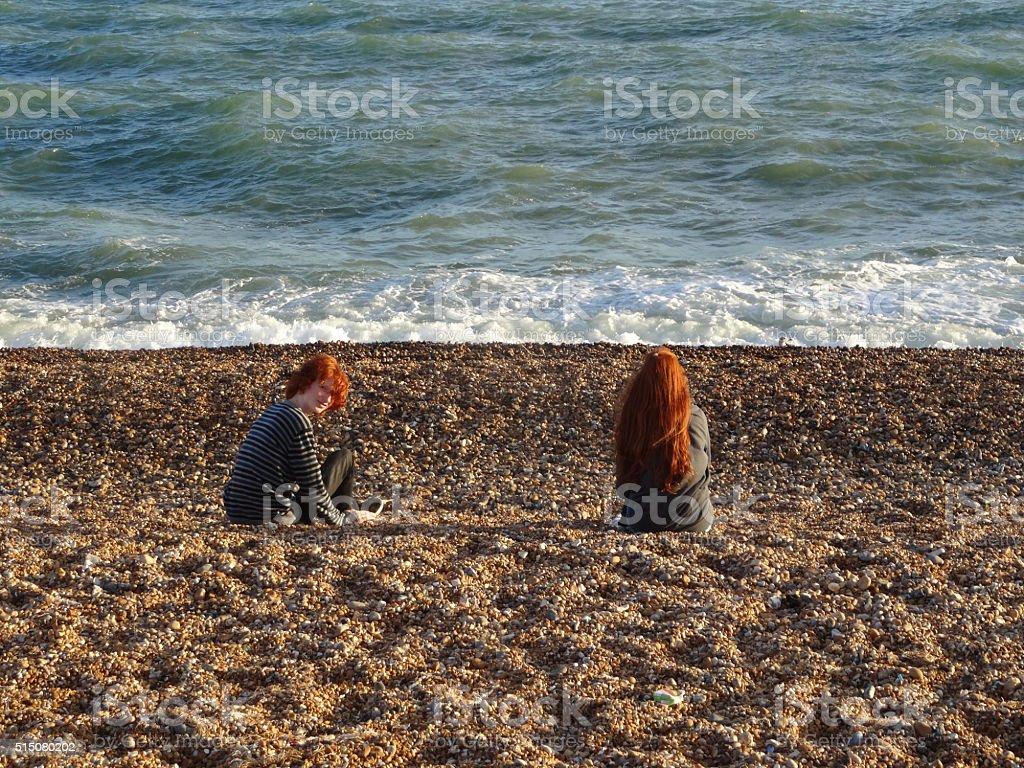 Image of children sitting on sandy seaside beach, by sea stock photo