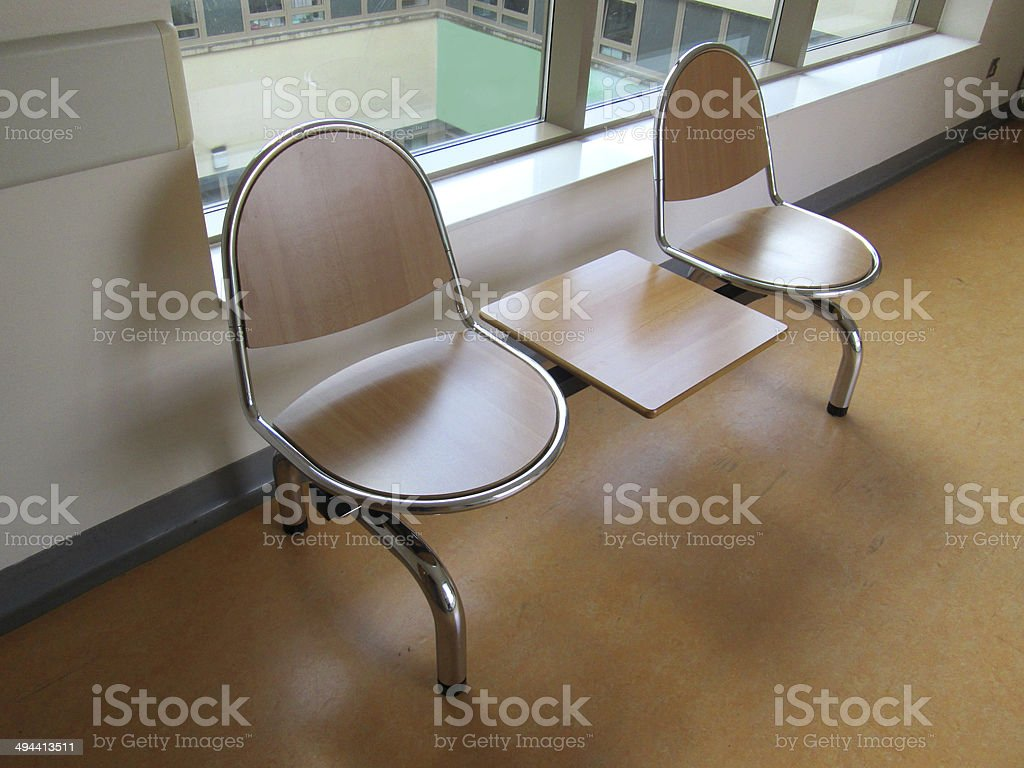 Image of chrome and wooden seats in a hospital corridor stock photo