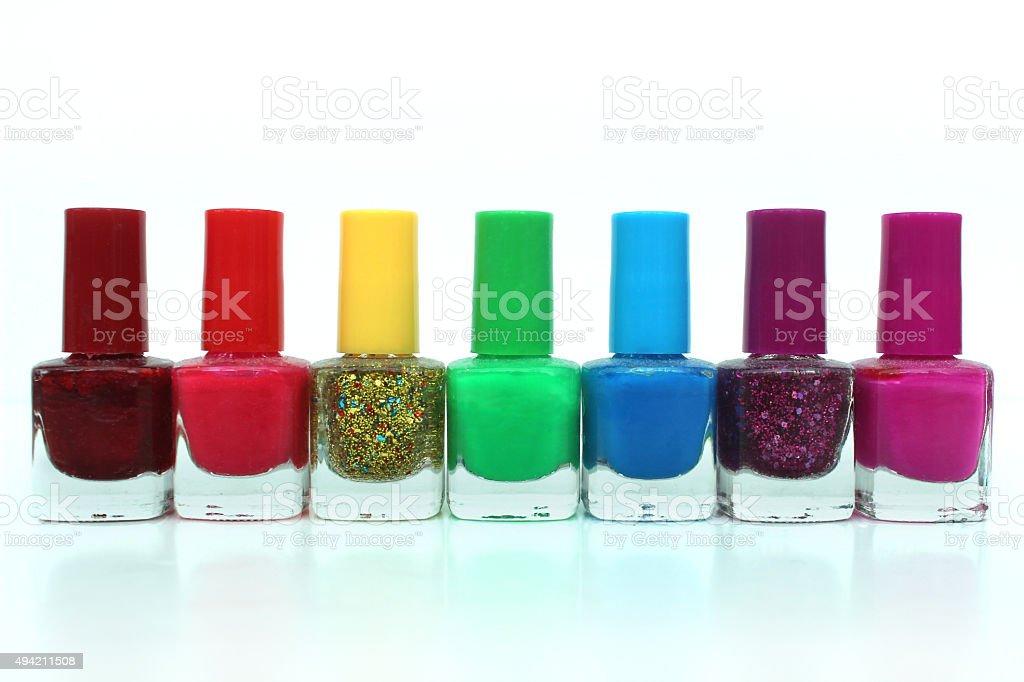 Image of colourful rainbow nail varnish bottles against white background stock photo