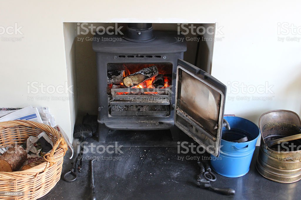 Image of contemporary fireplace with iron wood burning stove, log-basket stock photo