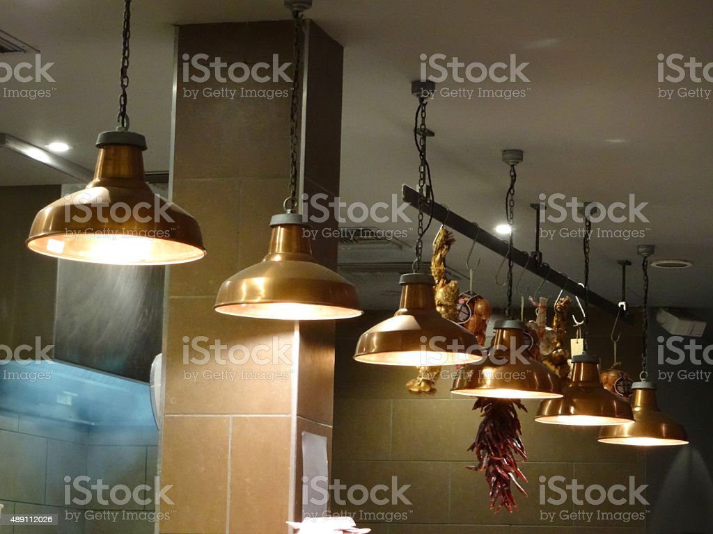Image of copper hanging lamps / lights in row, restaurant kitchen stock photo