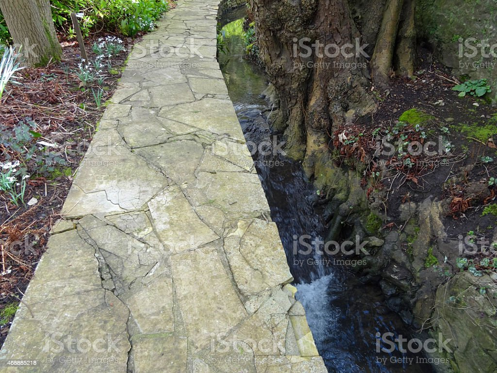 Image of crazy paving pathway in landscape garden, by stream stock photo