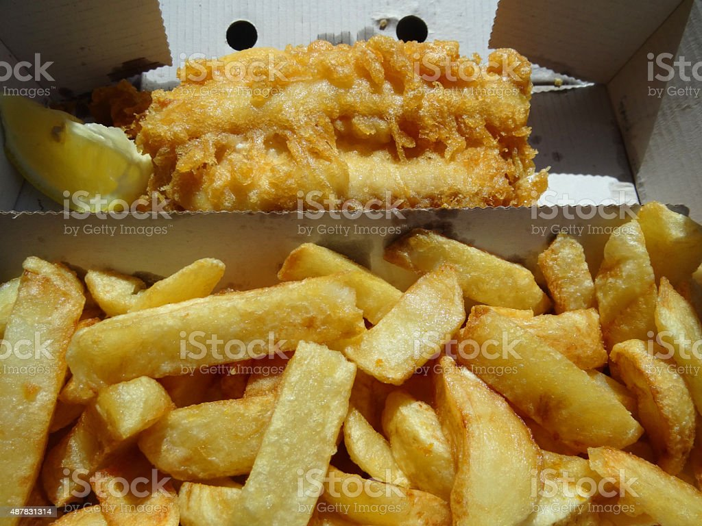Image of crunchy fish and chips in takeaway cardboard box stock photo