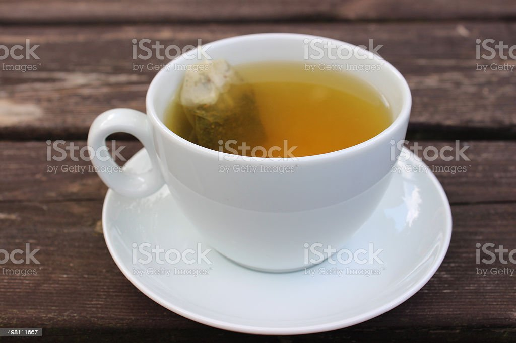 Image of cup of green tea, white cup, saucer, teabag stock photo