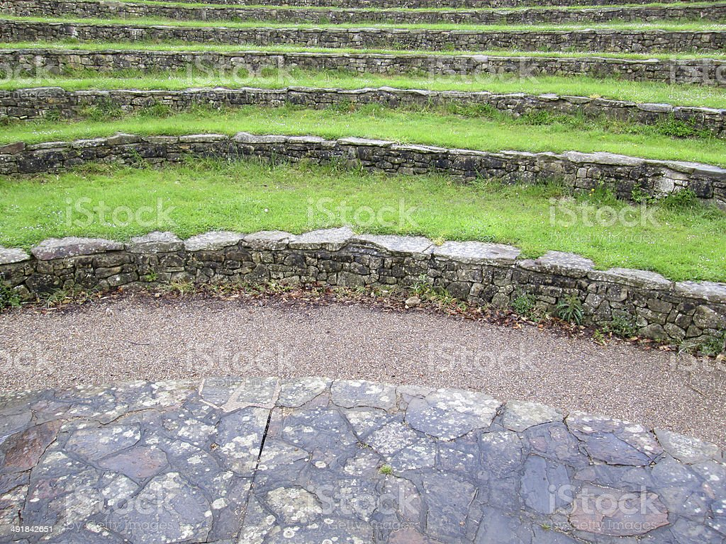 Image of curved stone and grass seats at outdoor amphitheatre stock photo