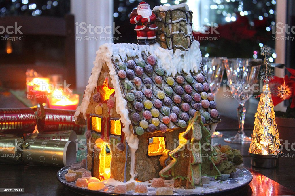 Image of decorated gingerbread house at night, lit with Christmas-candles stock photo