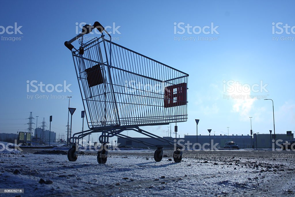 Image of empty shopping cart on empty parking near huge store stock photo