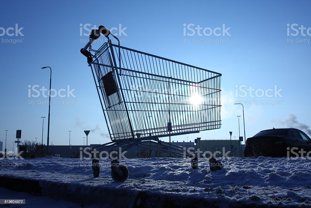 Image of empty shopping cart on parking near huge store stock photo