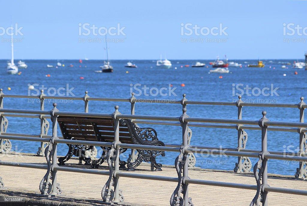 Image of English seaside, stone jetty / pier, Victorian railings, bench stock photo