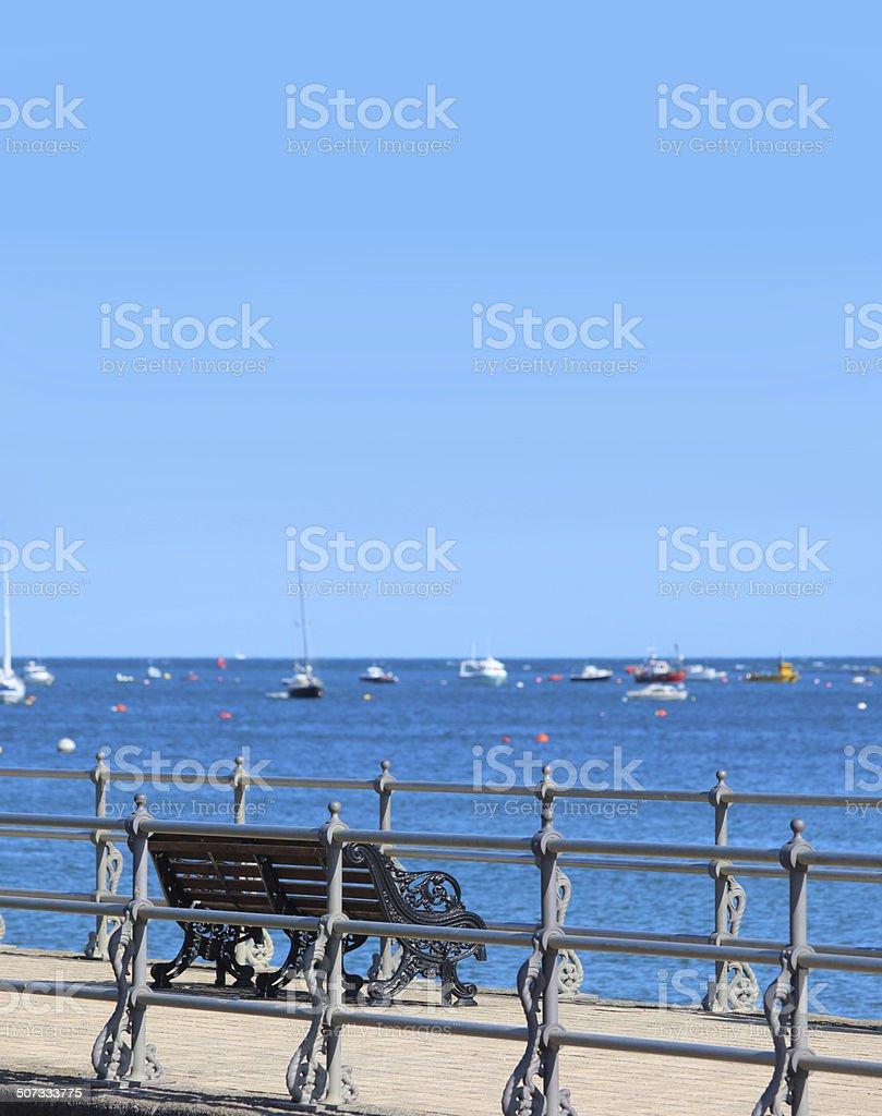 Image of English seaside, stone jetty / pier, Victorian railings, bench royalty-free stock photo