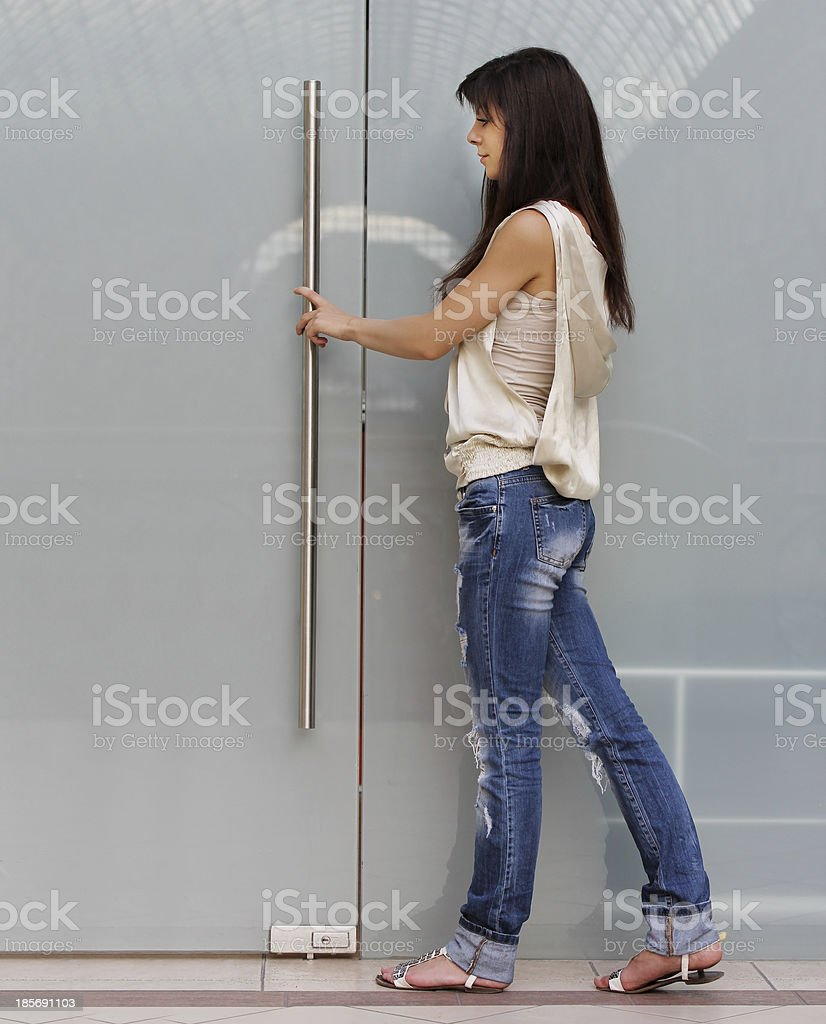 Image of  fashionable young woman trying to open the door stock photo