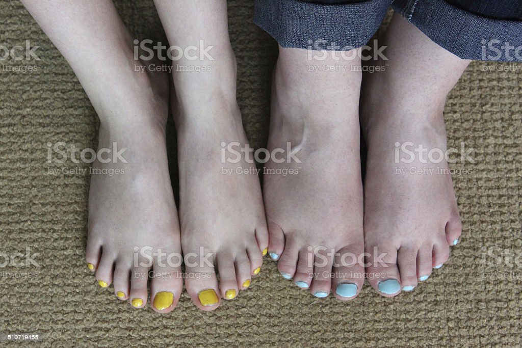 Image of feet, toenails painted with nail varnish, blue / yellow stock photo