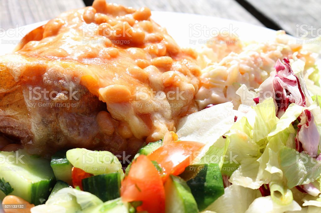 Image of filled baked potato, baked beans and grated cheese stock photo