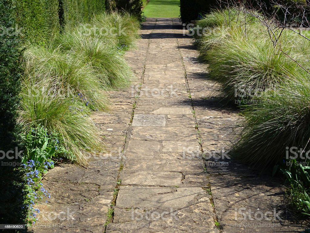 Image of flagstone pathway in garden with ornamental grasses / flowers stock photo