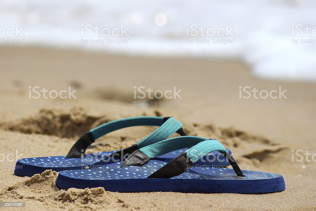 Image of flip-flops / thongs on sand at seaside, beach sandals stock photo