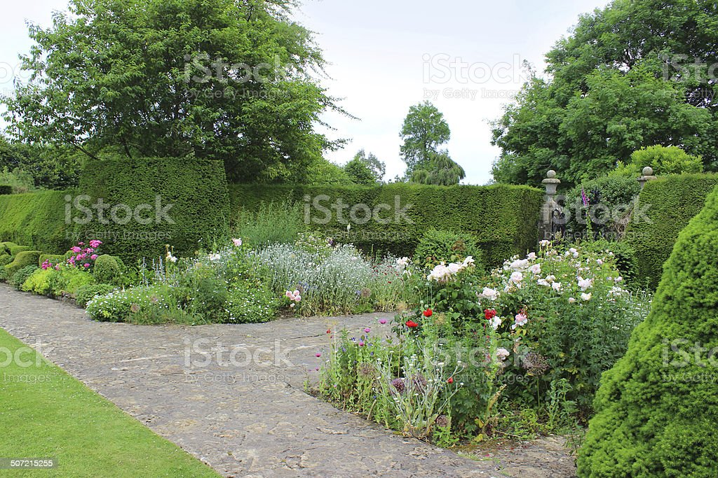 Image of formal garden, iron gate, yew hedge, herbaceous-border, roses royalty-free stock photo