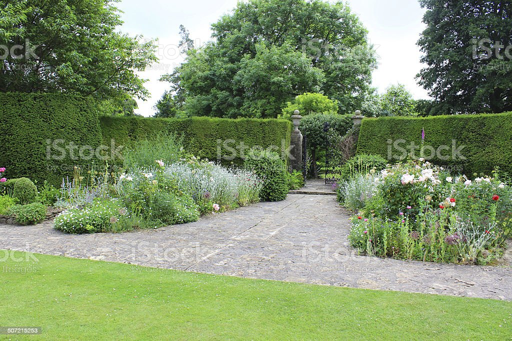 Image of formal garden, iron gate, yew tree hedge, herbaceous-border royalty-free stock photo